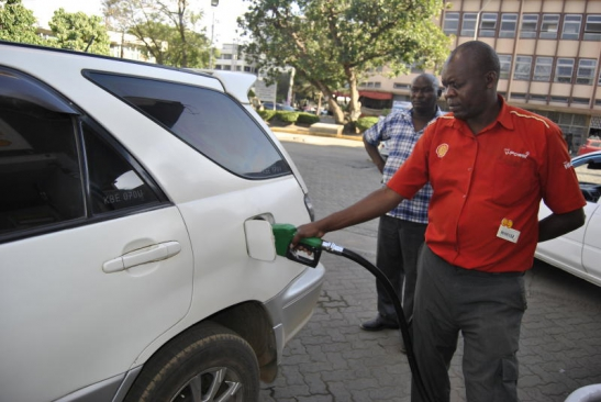 A petrol station attendant in Nakuru fuels a car on January 15, 2015. The latest drop will see motorists pay Sh85.49 per litre for super petrol. PHOTO: KIPSANG JOSEPH/STANDARD