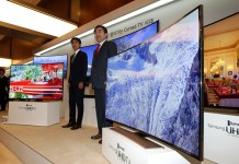 Staff members of Samsung Electronics introduce an Ultra High Definition (UHD) curved television during Samsung Electronics' new product media day event at the company's headquarters in Seoul, South Korea, Feb. 20, 2014. (Xinhua/Park Jin-hee)