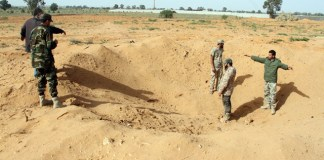 Libya Dawn fighters check a crater left by an air raid in the Tarhuna area, 80 km southeast of Tripoli, Libya, on March 23, 2015. Libyan national army's warplanes launched an airstrike on Tarhuna, attempting to pound the stronghold of Libya Dawn. (Xinhua/Hamza Turkia)