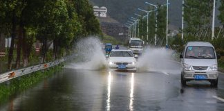 Cars ride on a road submerged by water in Sanmen County of east China's Zhejiang Province, July 11, 2015. The approaching Typhoon Chan-Hom has brought gales and rainstorms to Zhejiang Province, east China, forcing hundreds of flights to be canceled and highways to be closed, local authorities said Saturday. (Xinhua/Xu Yu) (zwx)