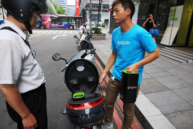 A staff member shows battery change on a gogoro motorcycle or Smartscooter for a driver at a battery station in Taipei, southeast China's Taiwan, July 17, 2015. The Smartscooter is designed to be able to run 100 kilometers at a speed of 40 kilometers per hour powered by two batteries. Customers can get fully-charged batteries by swapping batteries at 32 battery swap stations in Taipei. The number of the stations are expected to rise to 150 by the end of this year. (Xinhua/Cai Yang) (lfj)