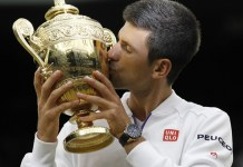 Novak Djokovic of Serbia kisses the trophy after the men's singles final with Roger Federer of Switzerland at the 2015 Wimbledon Championships in Wimbledon, southwest London, Britain on July 12, 2015. Novak Djokovic beat Roger Federer 3:1 to win the title. (Xinhua/Han Yan)