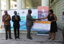 acting Chief Director of Ministry of Agriculture receiving a dummy cheque from a Rep from Dizengoff company.