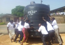 Old students of KPASEC lifting the 10,000 litre capacity water reservoirs