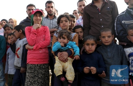 Syrian refugees stand as they gather during the visit of United Nations Secretary-General Ban Ki-Moon to al-Dalhamiyeh camp in the Bekaa Valley, Lebanon March 25, 2016. REUTERS/Aziz Taher