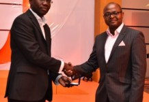 Mr Julian Kingsley Opuni, Divisional Director for Retail Banking, presenting a gold coin to a winner during the customer appreciation draw