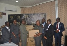Dr Dzanie (3rd from left) presenting the laptop to the VC, Prof Ampiah