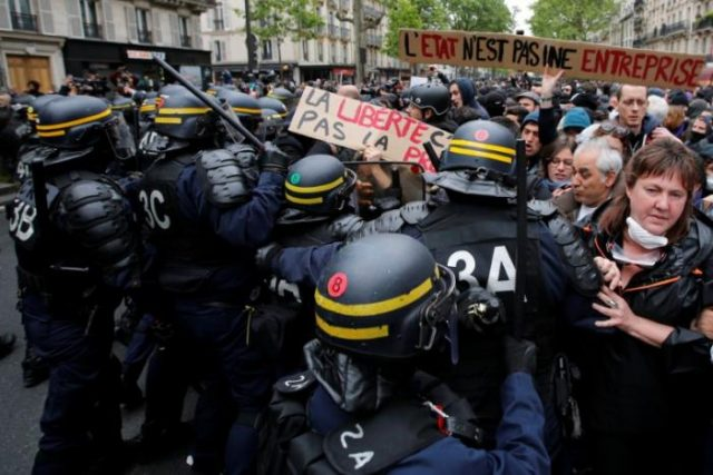 French riot police surround demonstrators who hold a placard with the message,