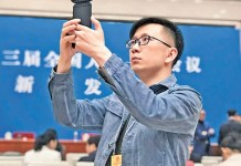 A People's Daily journalist records a virtual reality panorama video at the press conference for the first session of the 13th National People's Congress. (Photo: People's Daily)