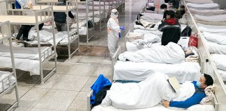 Patients infected with the novel coronavirus are seen at a makeshift hospital converted from an exhibition center in Wuhan, central China's Hubei Province, Feb. 5, 2020. The makeshift hospital converted from an exhibition center in China's epidemic-hit Wuhan city began accepting patients Wednesday. The hospital can provide about 1,600 beds to infected patients. (Xinhua/Xiong Qi)