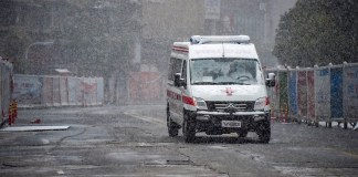 An ambulance drives on the street of Xiaogan, central China's Hubei Province, Feb. 15, 2020. Xiaogan witnessed a snowfall on Saturday as people around the city still fight in the battle against the novel coronavirus. (Xinhua/Hu Huhu)