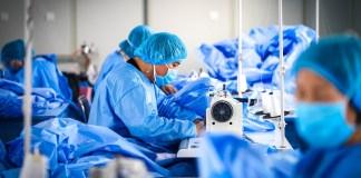 Workers make protective suits at Harbin Taigu Industrial Co., Ltd. in Harbin, northeast China's Heilongjiang Provinice, Feb. 15, 2020. (Xinhua/Wang Song)