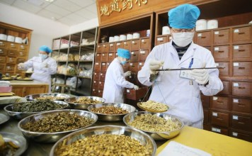 Pharmacists at a traditional Chinese medicine hospital in Nantong, east China's Jiangsu province dispense medicines according to prescriptions of a kind of Chinese herbal tea which has proven effective on the prevention of COVID-19, March 5, 2020. Xu Peiqin/People's Daily Online