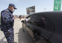 A Palestinian policeman speaks to a driver at a checkpoint at the entrance of the West Bank city of Nablus, March 23, 2020. Palestinian authorities on Sunday declared a 14-day lockdown on the West Bank as part of measures to combat the spread of coronavirus pandemic. Prime Minister Mohammed Ishtaye announced a ban on transportation and movement between the West Bank districts, urging citizens to stay at home. (Photo by Nidal Eshtayeh/Xinhua)