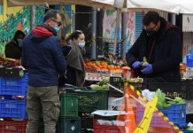 People wearing face masks shop for food at a market in Rome, Italy, on April 2, 2020. The number of confirmed COVID-19 cases worldwide has risen above 1 million, according to a new tally from Johns Hopkins University on Thursday. (Photo by Elisa Lingria/Xinhua)