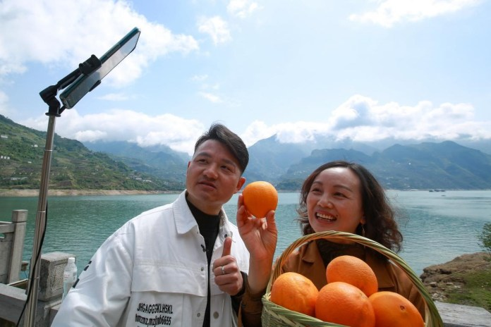 Employees of an e-commerce company in Yichang, central China's Hubei province promote navel oranges produced in Zigui, a county in Yichang on a livestream platform of social app WeChat, April 19. They have sold 50,000 kilograms of the navel oranges. Photo by Wang Gang, People's Daily Online