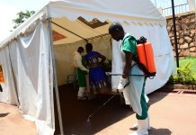 A health worker disinfects tent where people's temperature are checked at China-Uganda Friendship Hospital in Kampala in Uganda, March 27, 2020. Uganda has registered four new cases of COVID-19, bringing the total number of cases in the country to 18, according to the ministry of health. (Xinhua/Nicholas Kajoba)