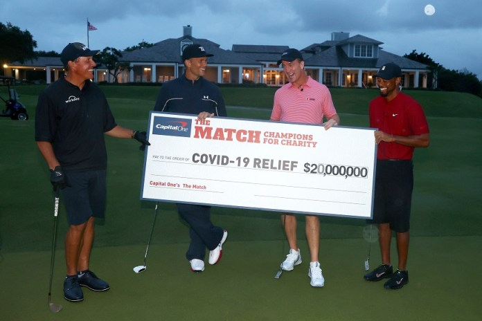 HOBE SOUND, FLORIDA - MAY 24: Tiger Woods and former NFL player Peyton Manning celebrate defeating Phil Mickelson and NFL player Tom Brady of the Tampa Bay Buccaneers on the 18th green during The Match: Champions For Charity at Medalist Golf Club on May 24, 2020 in Hobe Sound, Florida. (Photo by Mike Ehrmann/Getty Images for The Match)