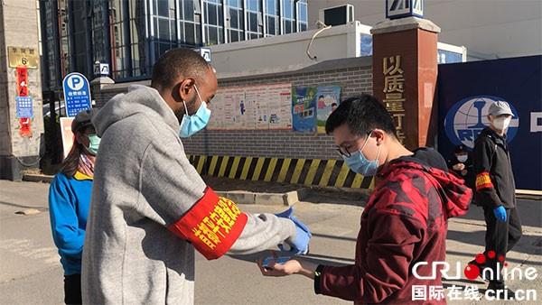 Ali Albade takes body temperature for a resident at the entrance of his community. Photo by China Radio International (CRI) with China Media Group