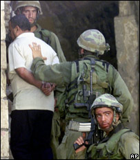 Israeli soldiers make a Palestinian resident enter a house in Nablus in August 2002