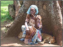 Ugandan spiritual medium sitting by a sacred tree