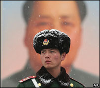 Soldier stands guard near portrait of late Chinese communist leader Mao Zedong