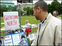 Adil Charkaoui walks past a number of protest signs outside the Ottawa court