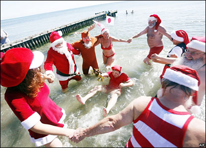 Santas cavort in the ocean at Bellevue beach in Copenhagen, Denmark