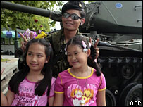 children pose with a soldier in central Bangkok