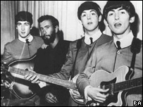 John Lennon (l), Paul McCartney (second right) and George Harrison (r) who is holding his guitar