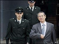 Alberto Fujimori escoltado por oficiales chilenos.