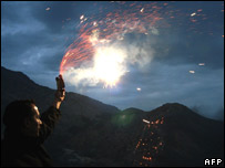 An Iraqi Kurd lights a firework as he celebrates Nowruz