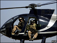 Blackwater security personnel on board a helicopter in Baghdad (2005). As many as 20,000 private security contractors are working in Iraq