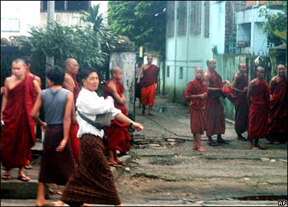 Monks watch armed police officer