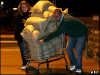 Residents push a shopping trolley full of sandbags