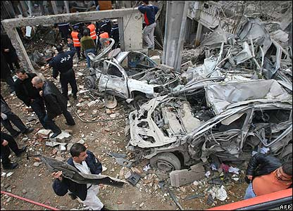 Rescue workers and bomb experts inspect damaged cars near the destroyed UN building