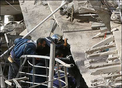 Rescue workers and bomb experts search a collapsed building for survivors