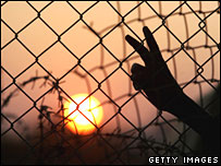 A boy flashes a V-sign next to the breached fence at Rafah between Gaza and Egypt