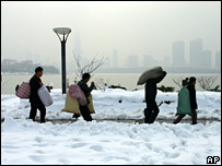 Migrant workers walk across snow-covered roads in Nanjing on 29 January 2008