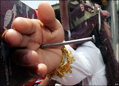 Philippine Catholic Penitents nail their hands to a cross to celebrate Good Friday...