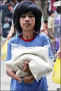 Joven filipino carga saco de arroz.