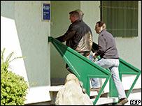 Dos oficiales trasladan a Joseph F. (centro) a la estación de polic�a.
