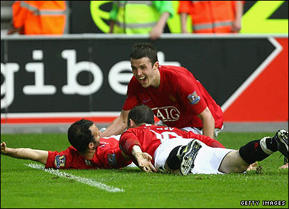 Ryan Giggs is mobbed by his team-mates after scoring United's second