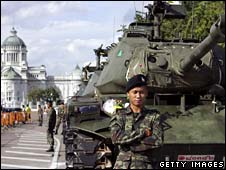 A Thai soldier stand next to a tank by a government building on 21 September 2006