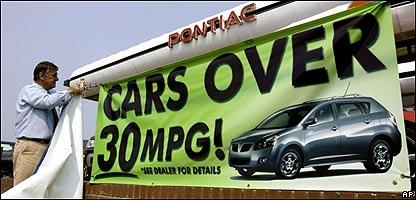El consultor de ventas de General Motors,  Mike Bechtolt, cuelga una pancarta en frente de la concesionaria de GM en Portland, Oregon, AP