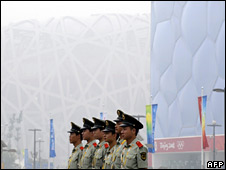 Security personnel stand in front of a Bird's Nest stadium hidden by haze on 7 August 2008