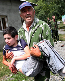 A man carries a boy, who was injured in South Ossetian regional capital Tskhinvali (9 August)