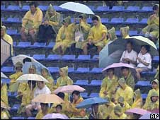 Empty seats dot the stadium as spectators await the start of the rowing competitions under heavy rain at the Beijing 2008 Olympics in Beijing on Sunday