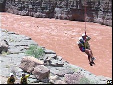 A stranded rafter is lowered to shore by a National Park Service employee after being hauled across the Colorado River in the Grand Canyon, 17 August 2008