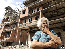 A Georgian woman stands near a damaged apartment block in Gori, Georgia